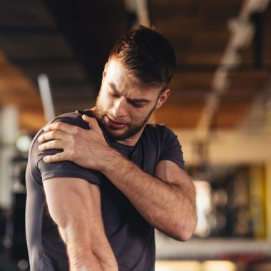 handsome young man feeling the pain in shoulder at the gym
