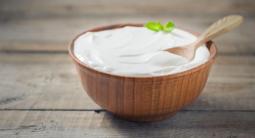 Greek yogurt in a wooden bowl on a rustic wooden table