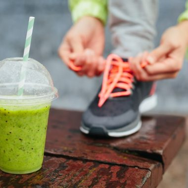 Green detox smoothie cup and woman lacing running shoes before workout